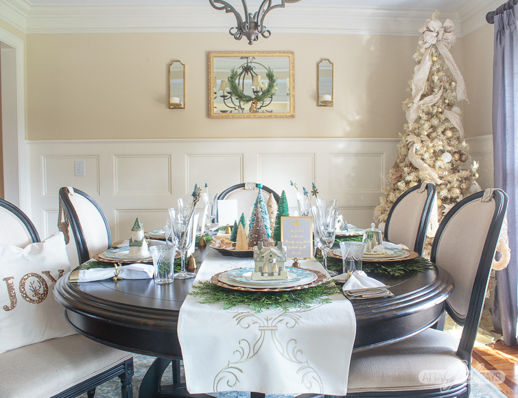 formal dining room decorated for Christmas with a gold tree