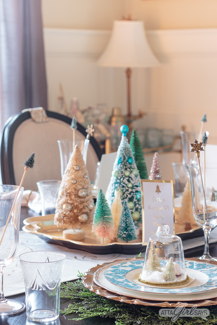 aqua and white bottlebrush Christmas trees on a gold tray on a dining room table with a gold bamboo bar cart in the background