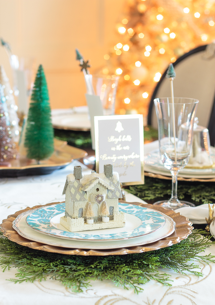 Christmas table decorations with a glittered putz house on top of an aqua china plate with a gold Christmas tree in the background