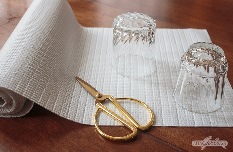 two glasses and scissors sitting on a roll of shelf liner