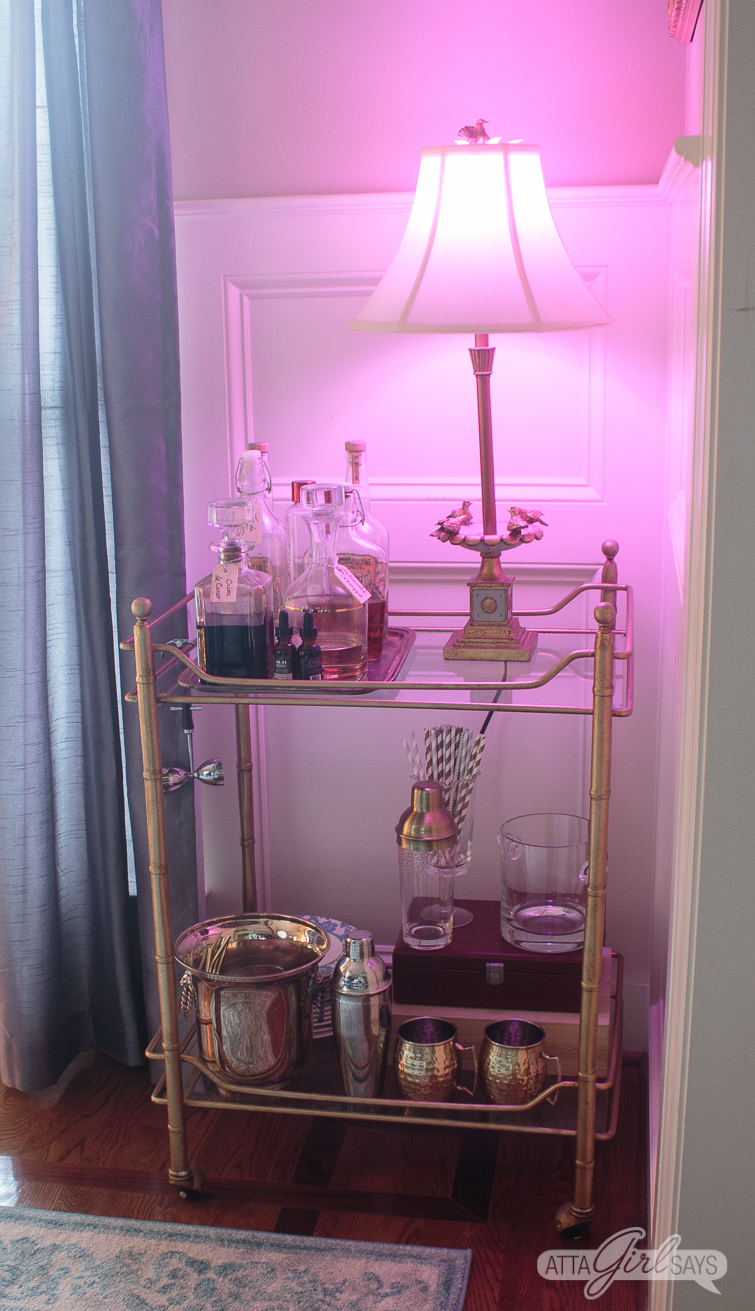 bar cart with a lamp with a pink color changing light bulb
