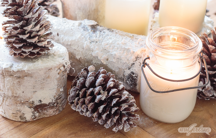 """winter table centerpiece with """"snowy"""" pinecones, birch logs and candles."""
