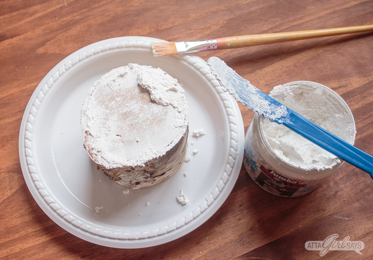 applying DecoArt Snow-Tex to a birch log with a paintbrush and a palette knife