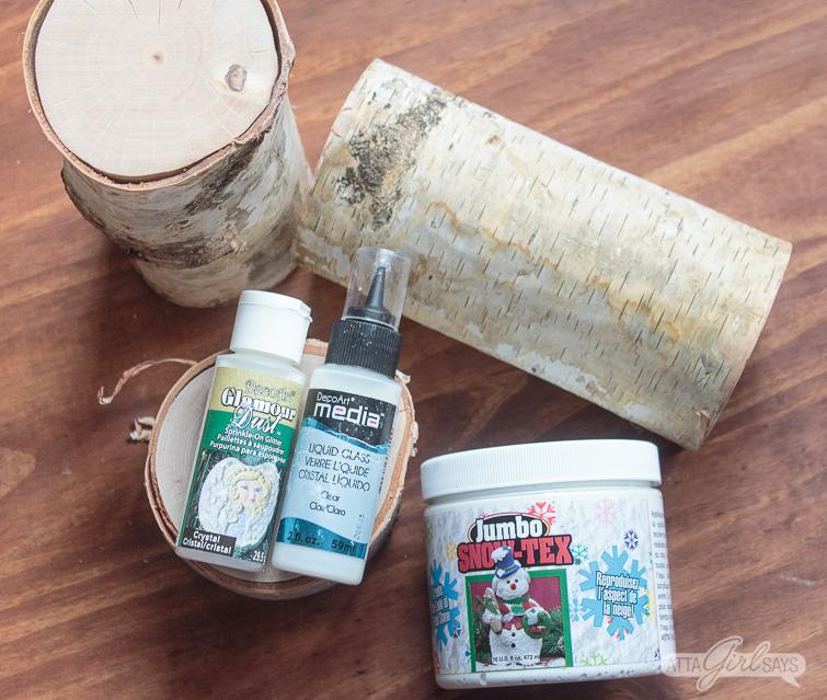 craft supplies including birch logs, sno-tex, glitter and Mixed Media Liquid Glass