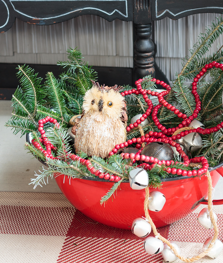 vintage red enamel bowl filled with Christmas greens, bells, red wooden beads and a woodland owl ornament