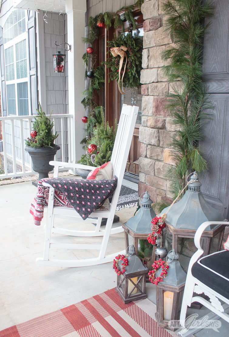 Christmas front porch with a white rocker, lanterns and an evergreen wreath on the front door