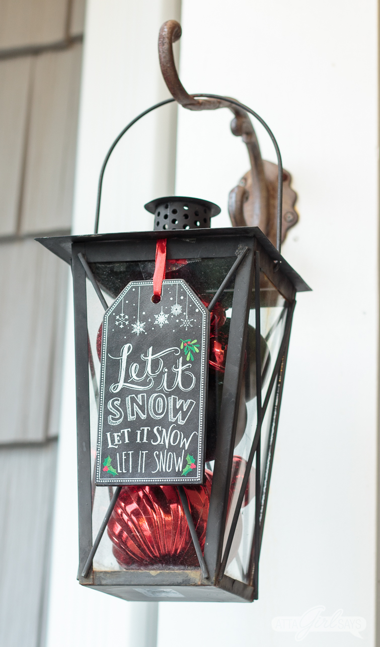 porch lantern filled with Christmas ornaments and adorned with a chalkboard tag