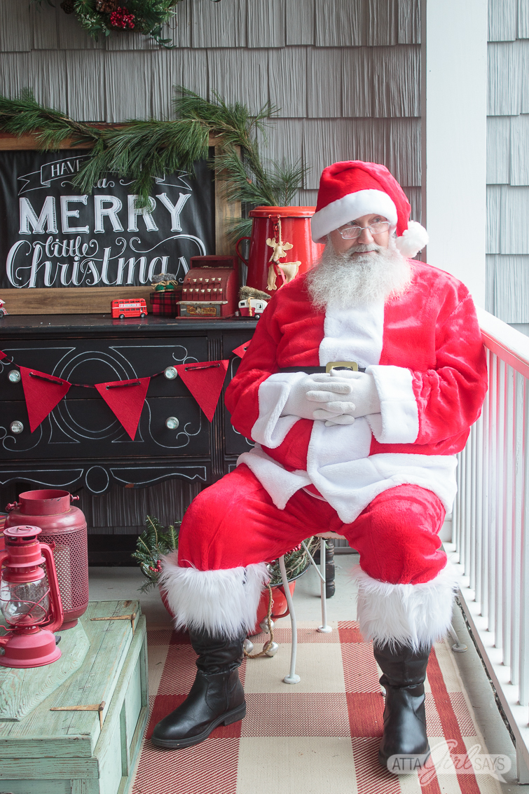 Santa Claus posing on a Christmas front porch in front of a black buffet and a chalkboard Merry Christmas sign