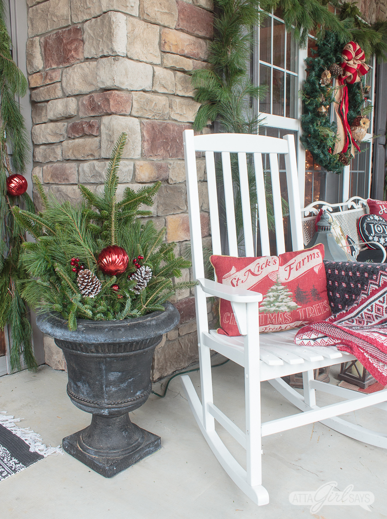 black urn planter filled with evergreen arrangement with pinecones and red Christmas ornaments sitting beside a white rocking chair on a porch