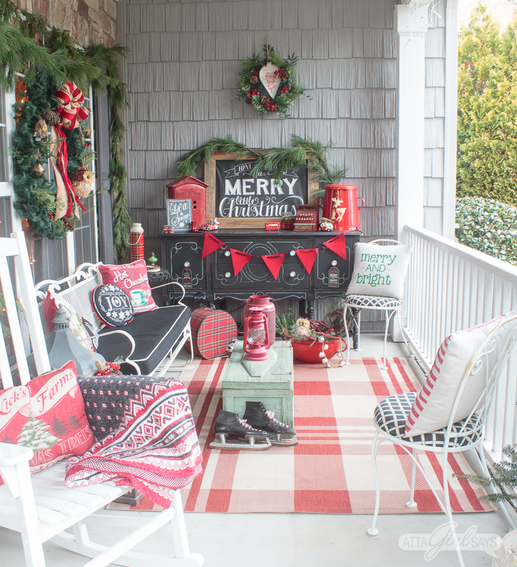 Christmas front porch decoratings, including a red plaid rug, a black painted buffet with vintage red accents