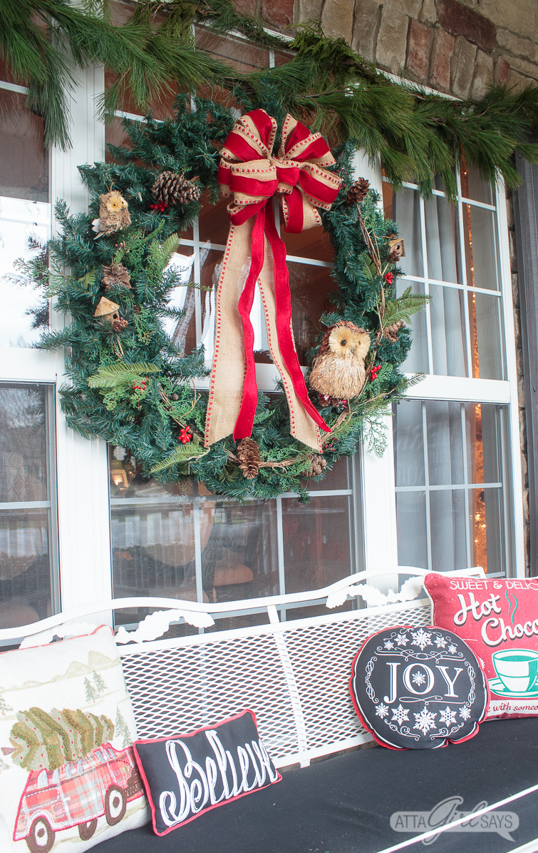 large wreath with a burlap bow on a front porch window