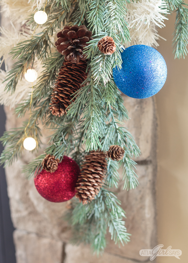 green and white Christmas garland decorated with red and blue ornaments and ball lights