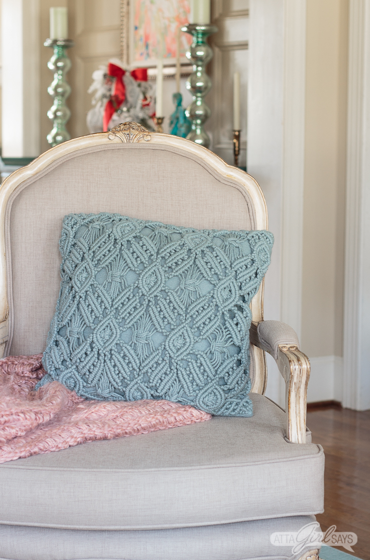 French bergere chair with a pink throw blanket and an aqua pillow on it