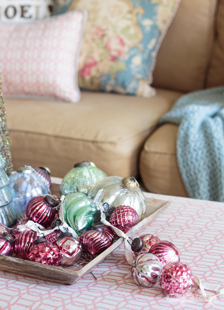 pink mercury glass garland and oversized Christmas ornaments on a tray in front of a sofa