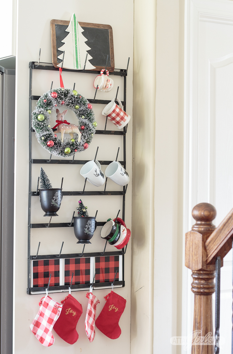Christmas mug rack decorated with mugs, buffalo check plates and a vintage wreath