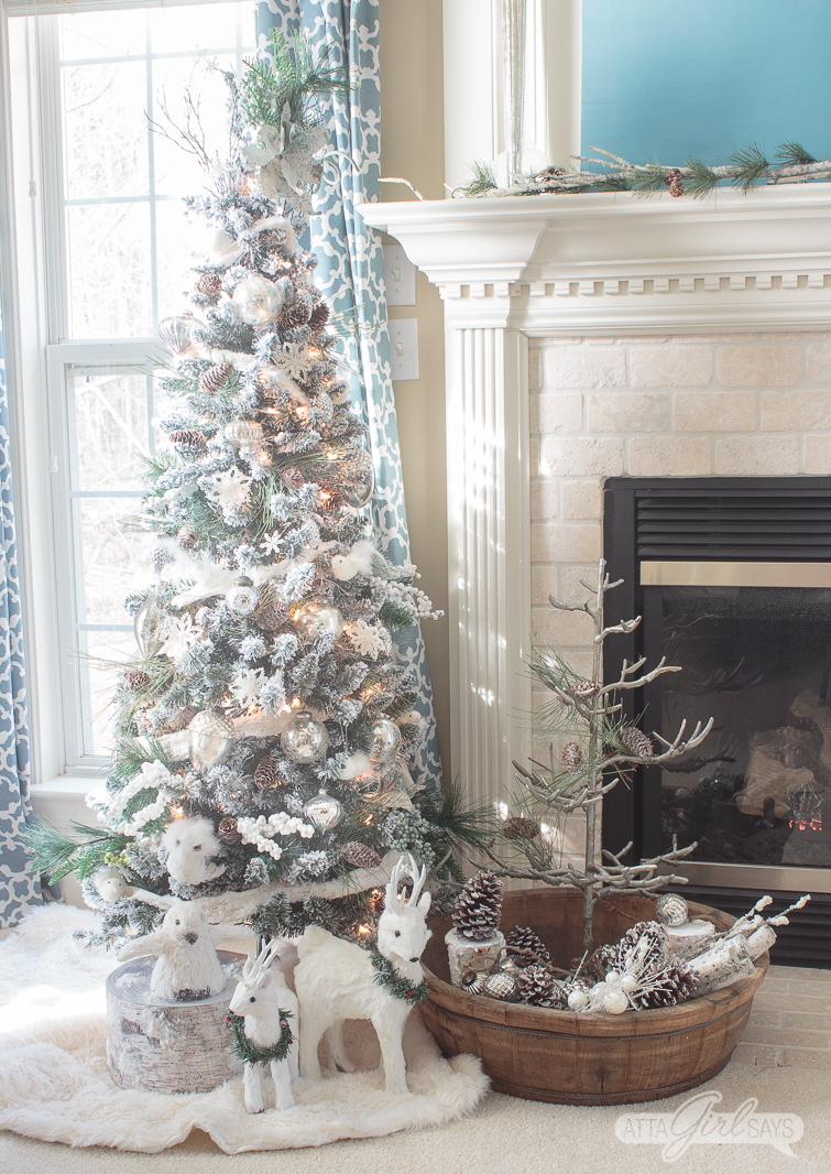 white flocked Christmas tree beside a fireplace in a bedroom with blue curtains