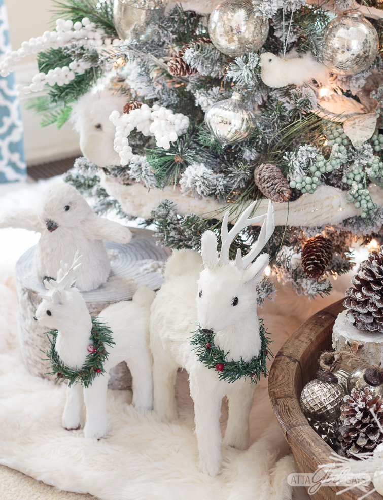 white deer at the base of a woodland Christmas tree