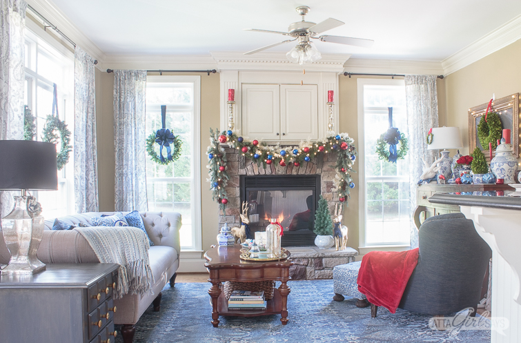 cozy family room with blue rug and a stone fireplace decorated for Christmas