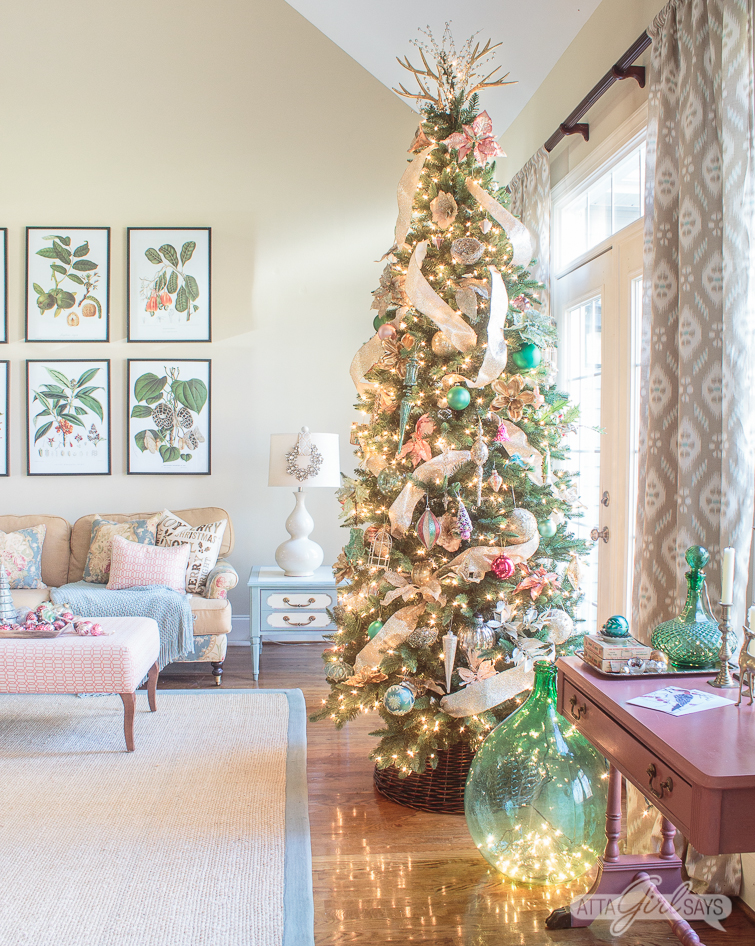 Christmas tree decorated with gold ribbon and pink and green ornaments in a formal living room