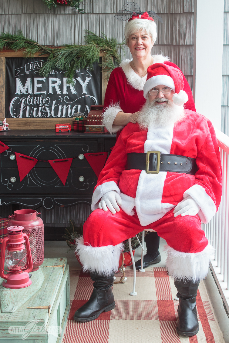 Santa and Mrs. Claus posing on a porch decorated in red, green and white vintage Christmas style