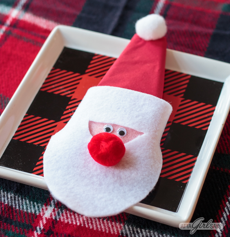 felt Santa Christmas napkin ring on a square buffalo check plate