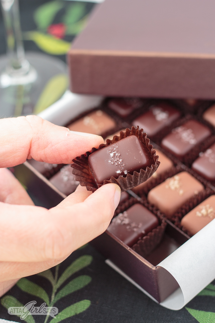 man's hand holding a chocolate salted caramel candy