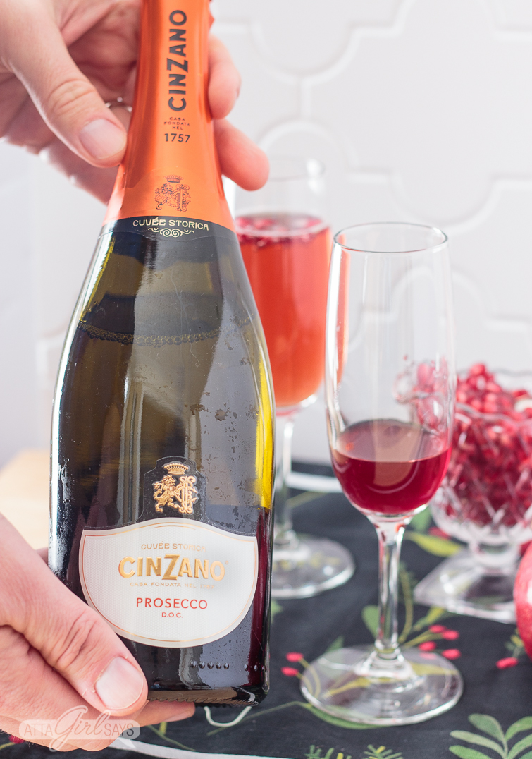 man holding a bottle of prosecco before making a pomegranate mimosa
