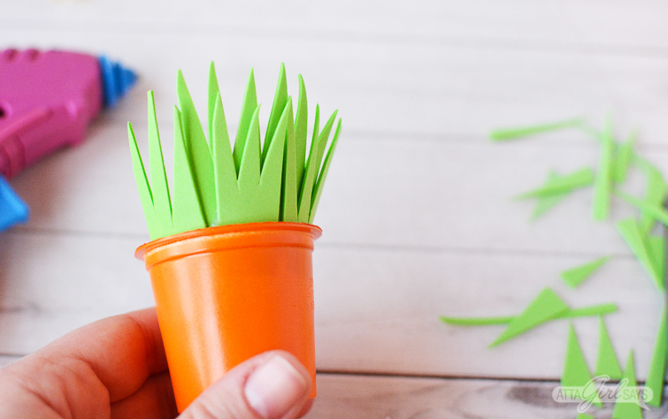 attaching foam grass to the tops of recycled K cup Easter carrot treat cups