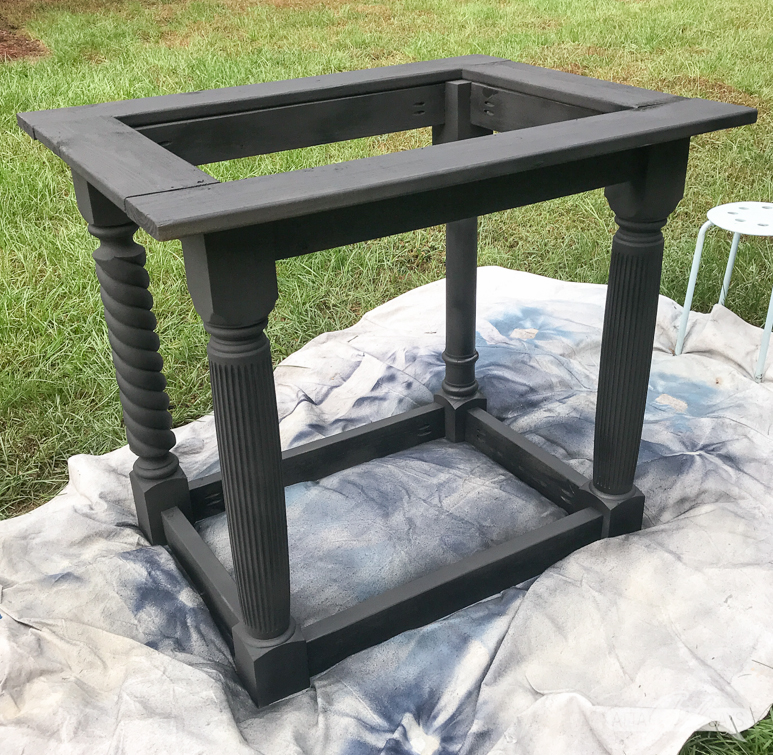 outdoor sink pedestal painted black on a dropcloth