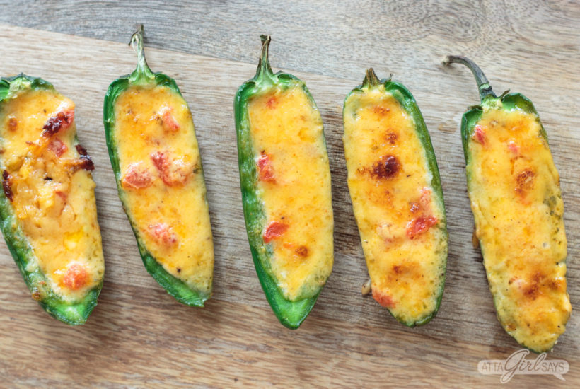 pimento cheese stuffed baked jalapeno peoppers on a cutting board
