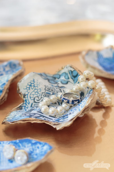 blue and white chinoiserie oyster shell jewelry dish with a pearl necklace resting on it