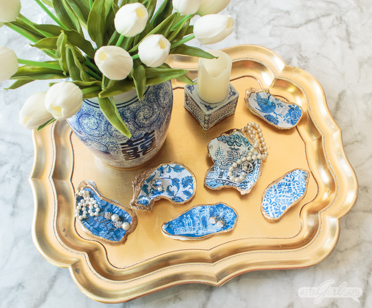 collection of blue and white oyster shells on a gold tray with a Chinese double happiness vase and other chinoiserie porcelain pottery