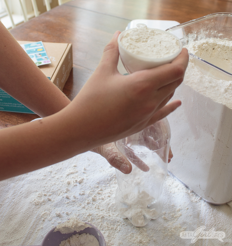 pouring flour into a plastic bottle using a funnel to make a DIY stress ball