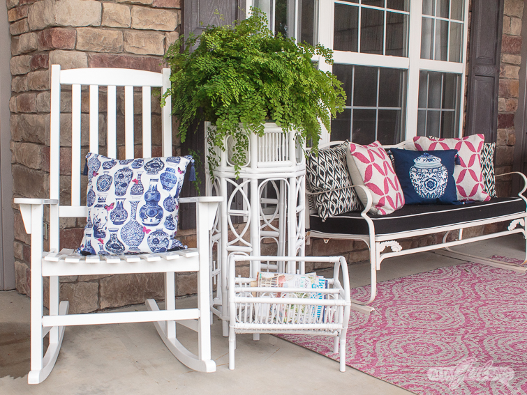 front porch decorated with white Hollywood regency furniture, a pink rug and blue chinoiserie pillows