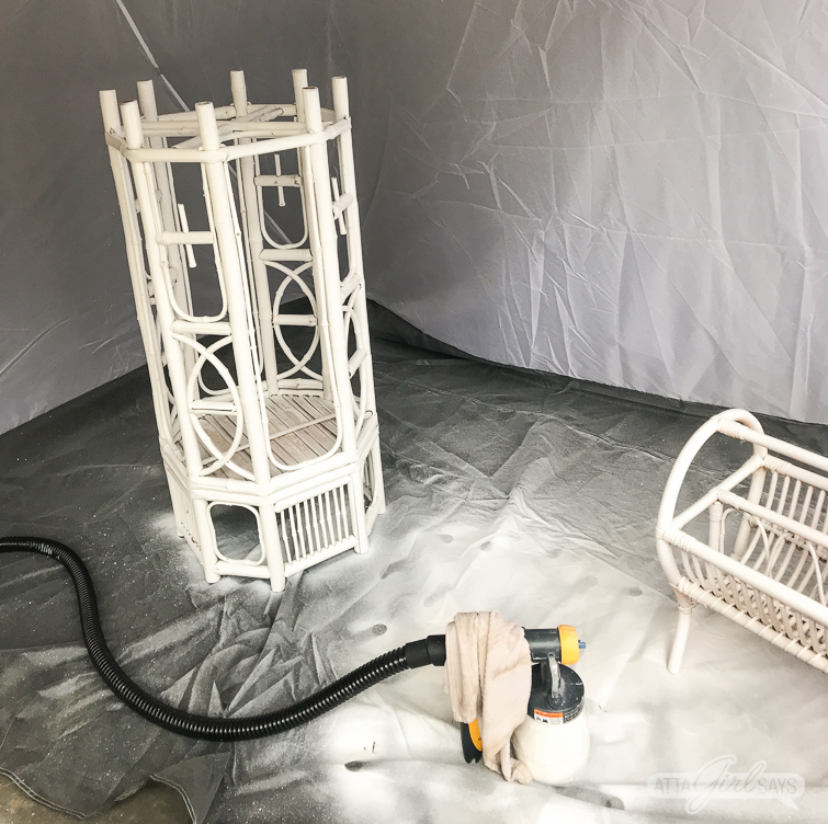 painting a bamboo and rattan plant stand and magazine rack with a sprayer in a spray tent