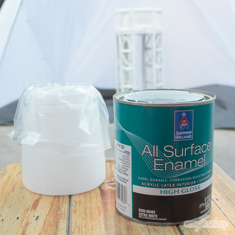 white furniture paint next to a plastic lined paint sprayer cup