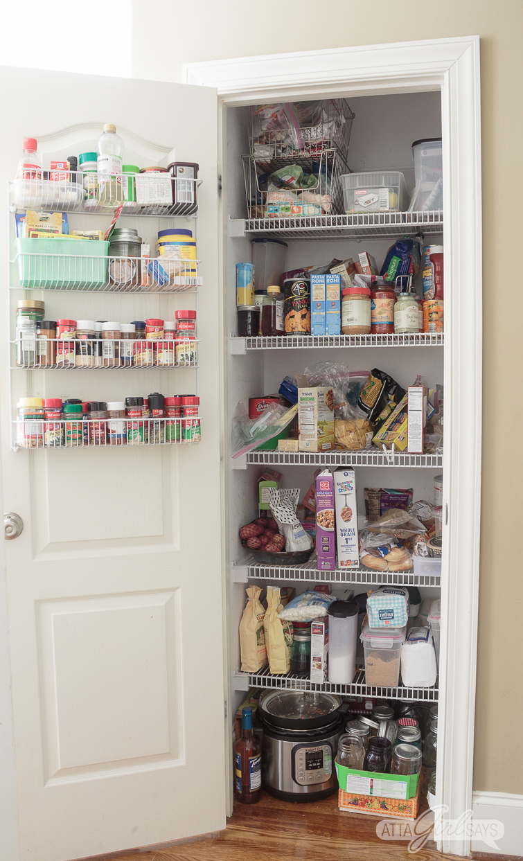 messy pantry with wire shelving and a door mounted spice rack