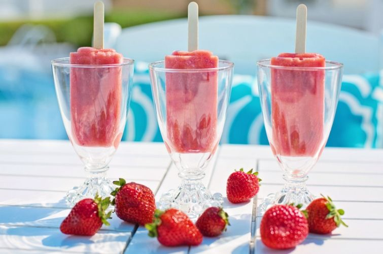 three strawberry popsicles in wine glasses