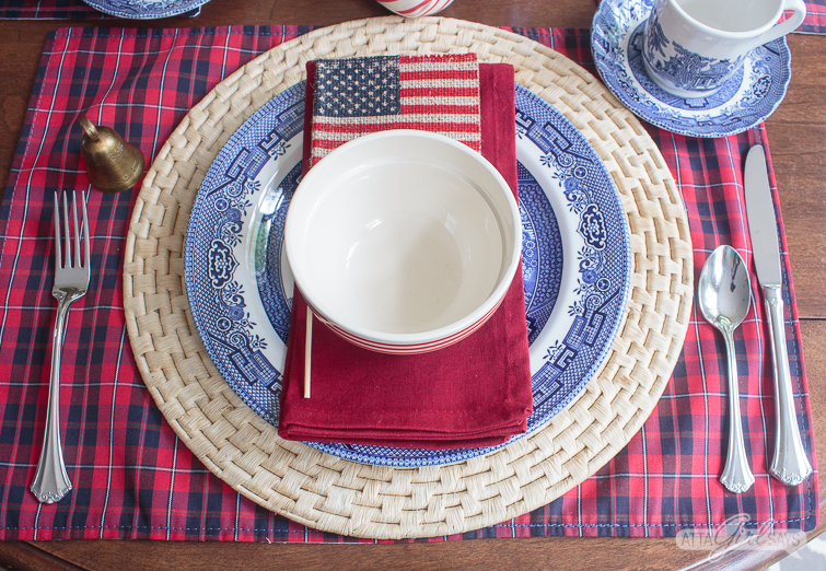4th of July table decoration with a Blue Willow Plate, red napkin, bowl and flag on a straw charger