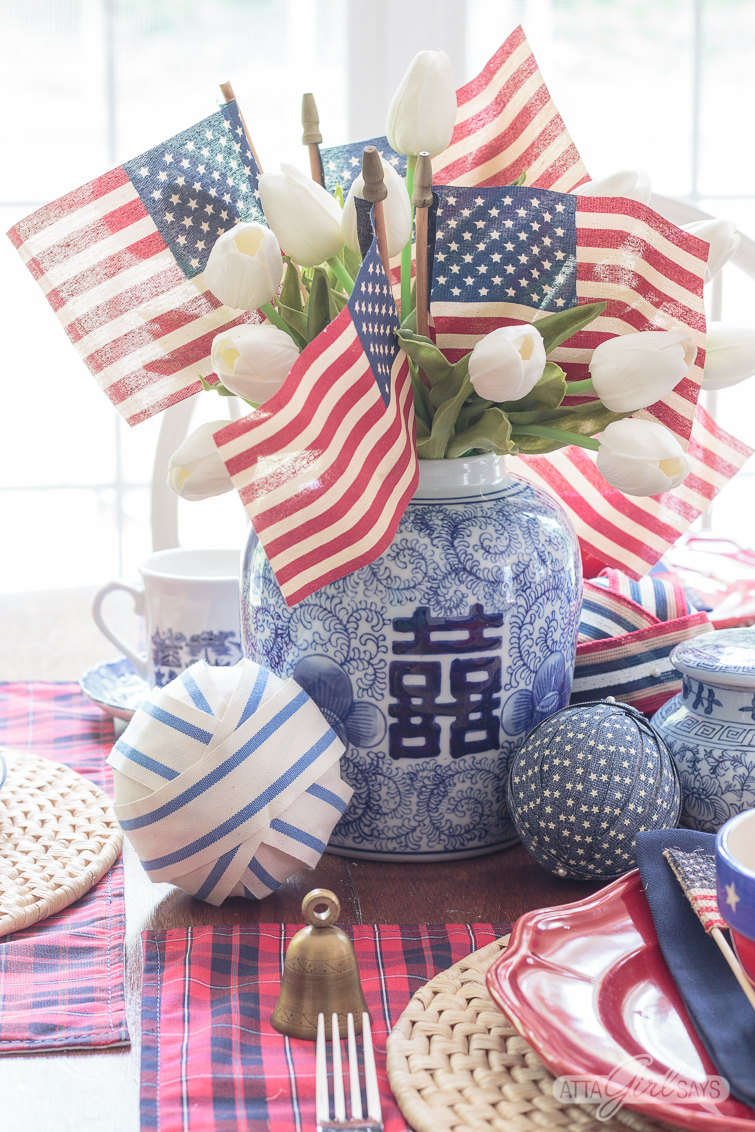 flags and tulips in a Chinese blue and white double happiness jar with other patriotic 4th of July table decorations