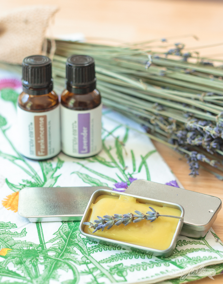 DIY lavender eye cream in a metal tin with essential oils in the background