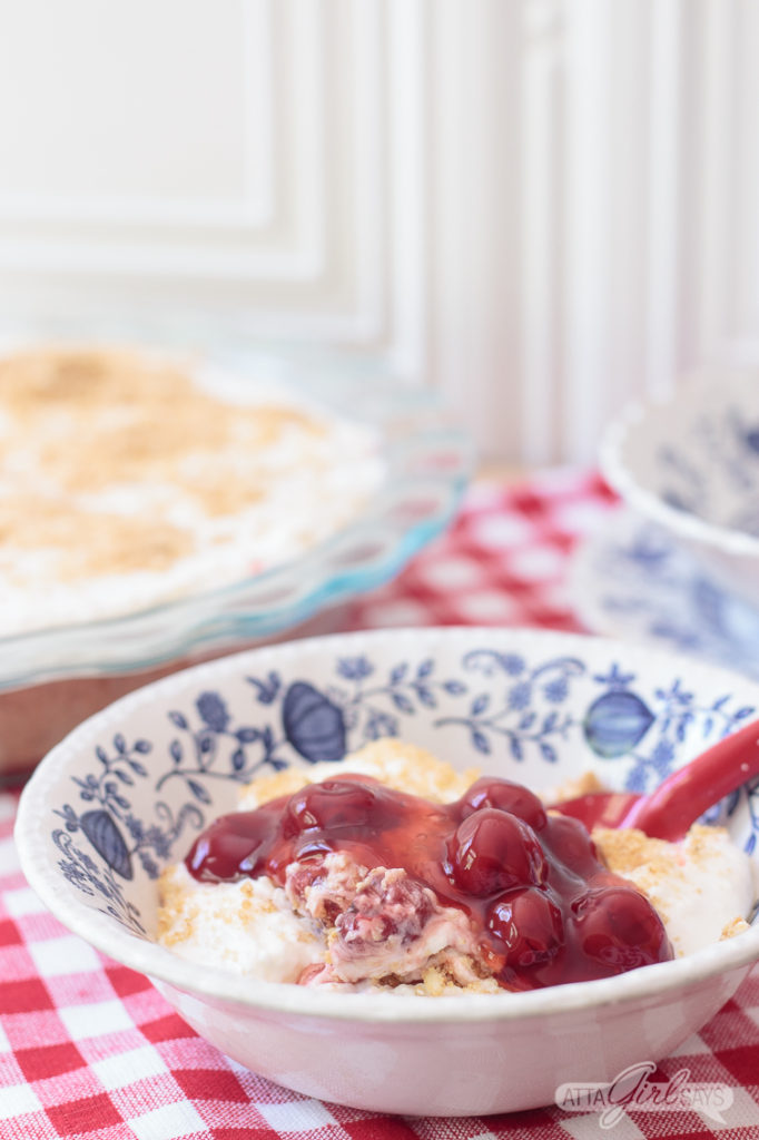 blue and white bowl with cherry yum yum dessert on a red gingham tablecloth