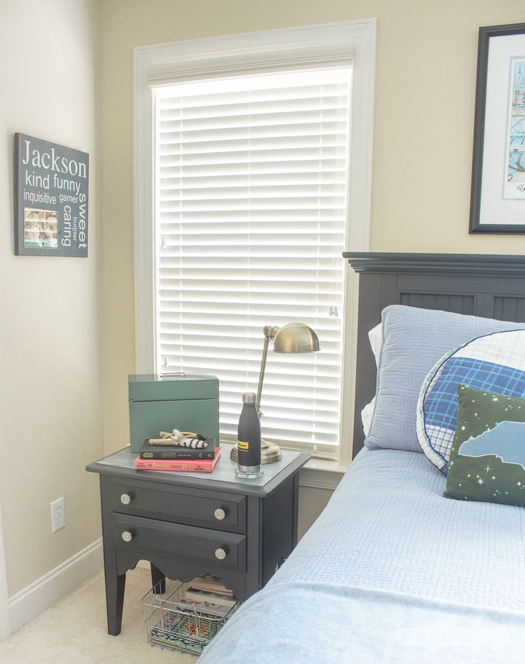boy's bedroom with dark gray bed and nightstand and blue bedding