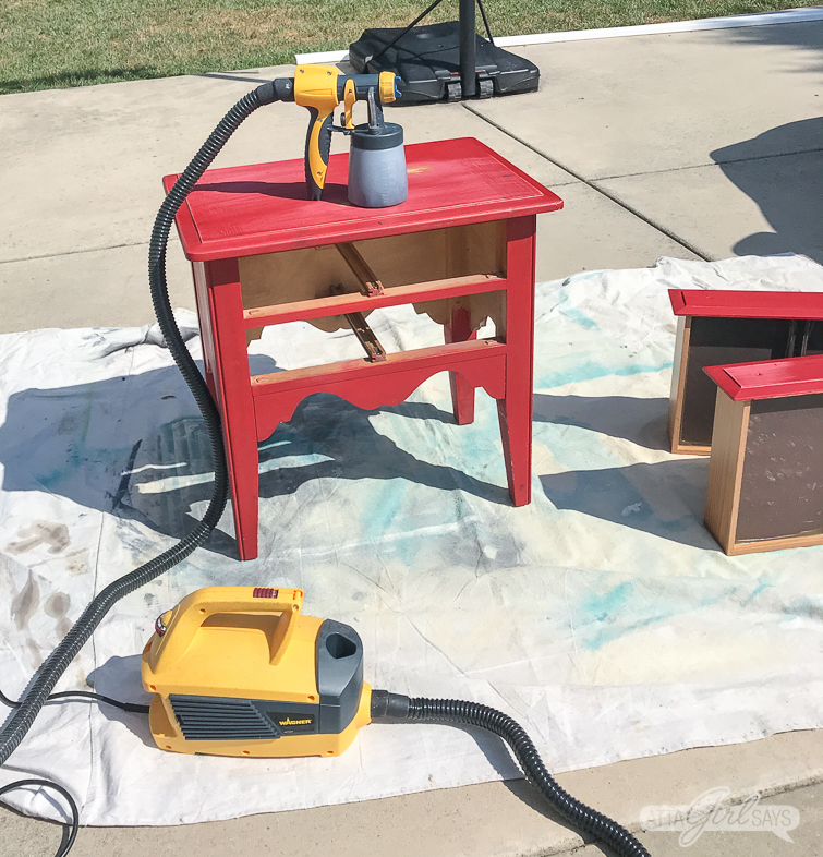 paint sprayer sitting on a red nightstand with two drawers on a dropcloth