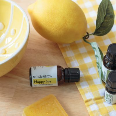 homemade lemon soap bar on a wooden countertop with Happy Joy essential oil blend, a lemon, a yellow gingham cloth and a lemon bowl