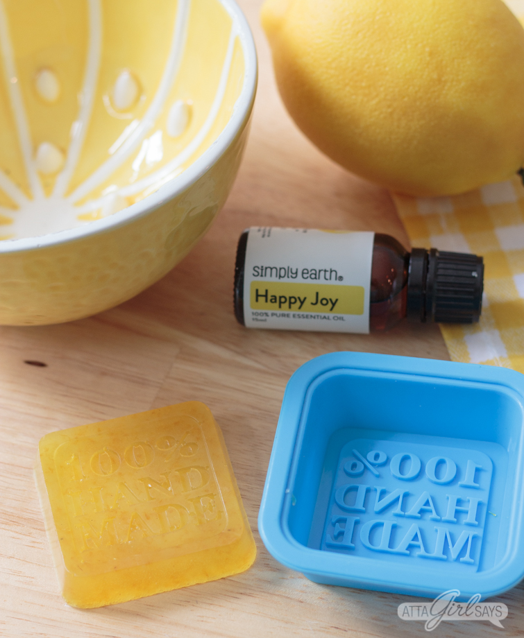 silicon soap mold and essential oil blend on a countertop with a homemade lemon soap bar