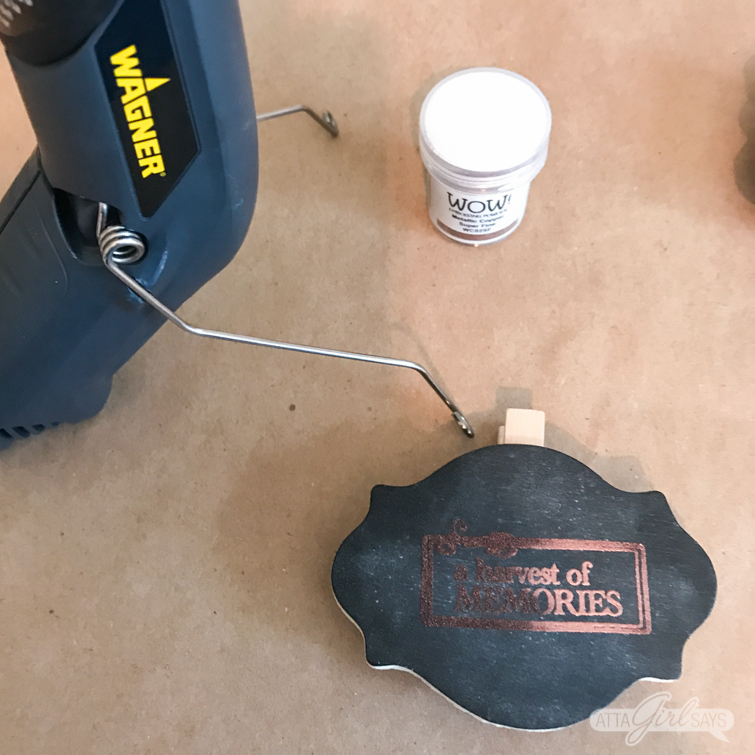 Using an embossing heat gun to emboss a metallic fall harvest design onto a wooden chalkboard clip