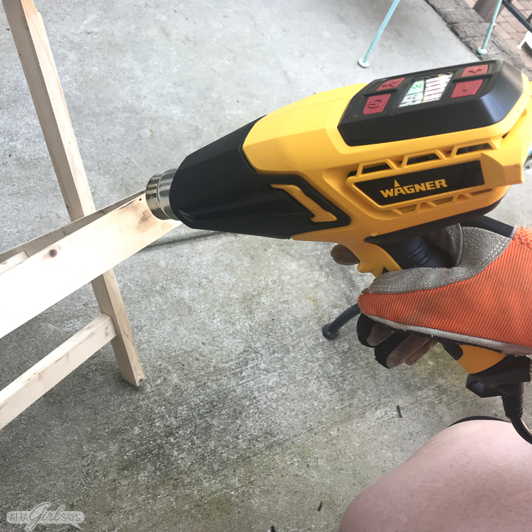 using a heat gun to create a burnt wood finish on a folding camp stool