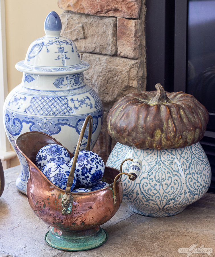copper bucket filled with blue and white carpet balls as part of fall fireplace decor