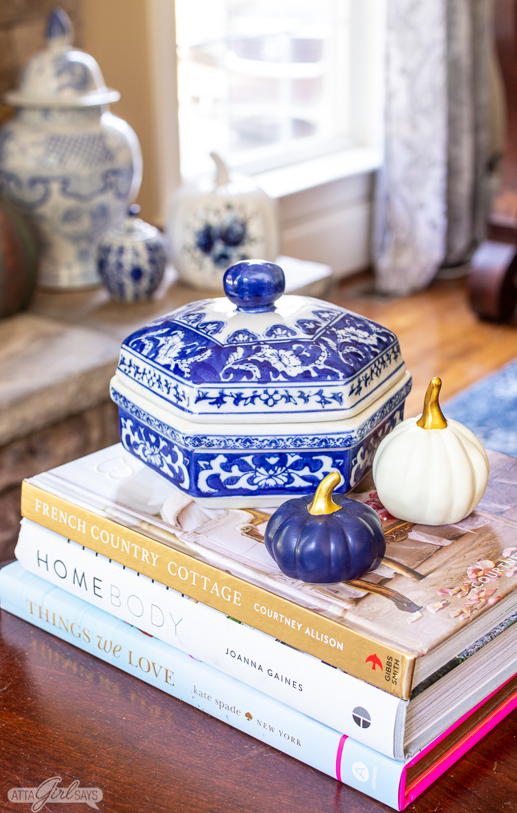 blue and white container and blue and white pumpkins sitting on home decor books